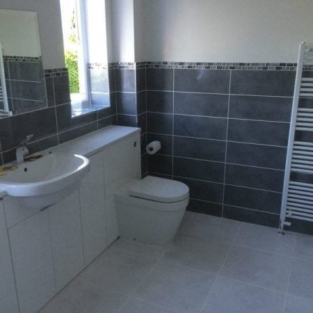 Bathroom fitting with toilet, towel radiator, sink and tiling